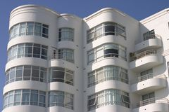 Art Deco Apartment Building #1. A large art deco apartment building displays it's face of curved windows and balcony's royalty free stock photography