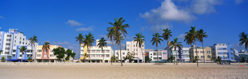 This is the art deco district of South Beach Miami. The buildings are painted in pastel colors surrounded by tropical palm trees. Royalty Free Stock Images