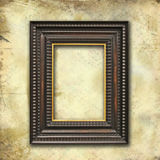 Art-deco empty frame on grunge texture. A wooden empty art-deco frame on a grunge wallpaper royalty free stock photos