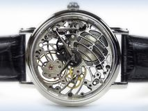 Art Deco Watch - Skeleton Movement. Art deco style wristwatch. The transparent case shows a skeleton movement on a white background Stock Image