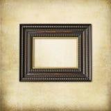 Art deco wooden empty frame. Jugendstil carved wooden frame with golden border on a grunge beige wall Royalty Free Stock Images