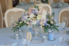 Art decor roses delphinium vase glasses cloth. Bouquet in a vase on the table with a tablecloth and candles rose white yellow and blue delphinium glasses plate Stock Images