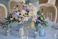 Art decor roses delphinium vase glasses cloth. Bouquet in a vase on the table with a tablecloth and candles rose white yellow and blue delphinium glasses plate Stock Photo