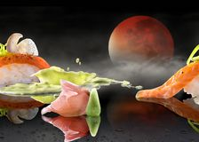 Sushi art design with bood moon. Art design picture of nigiri sushi with condiments ginger and wasabi with fog, wet mirror and a blood moon royalty free stock images