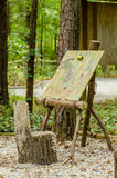 Art easel in forest. With a stump chair royalty free stock photo
