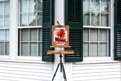 Art on an easel hillstead museum connecticut. A painting pf a tree in autumn on an easel outside of the hillstead museum in farmington Connecticut royalty free stock photos