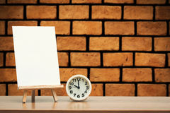 Art easel. Wooden easel with blank canvas and round clock on brick wall background Royalty Free Stock Image