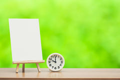 Art easel. Wooden easel with blank canvas and round clock on green nature background Stock Photography