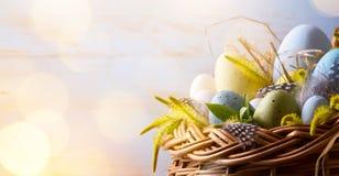 Art Easter-achtergrond met paaseieren in de mand stock afbeelding