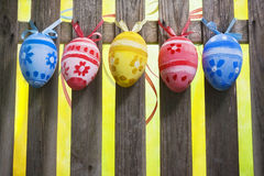Art easter background with eggs hanging on fence Royalty Free Stock Photos