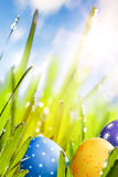 Art Easter eggs decorated in the grass. Art Colorful Easter eggs decorated in the grass on blue sky background stock photo