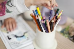 Art education and children activities concept. Hand of a little girl out of focus taking a pencil from a pencil jar full of colour pencils.Art education and Stock Photo