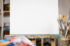 Art equipment: easel, brushes, tubes with paint, palette and paintings.  royalty free stock photography