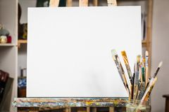 Art equipment: easel, brushes, tubes with paint, palette and paintings.  stock photo