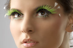 Art eyelashes. Cute portrait of a young beautiful woman with artificial green eyelashes stock image