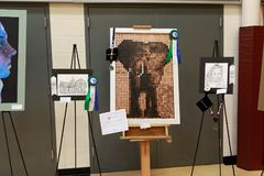 Art fair in local district school. Exhibition of works of art in a local district school showing a portrait, and sketch of buildings set upon a tripod and a stock image