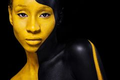 Black and yellow makeup. Cheerful young african woman with art fashion makeup. stock image