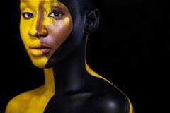 Black and yellow makeup. Cheerful young african woman with art fashion makeup. Art fashion makeup. An amazing woman with black makeup and leaking gold paint Royalty Free Stock Image