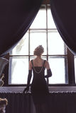 Art fashionable photo of beautiful girl staying at the window. Back view Royalty Free Stock Photography