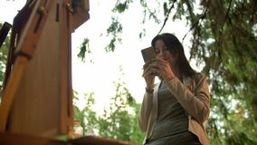 Art female painter texting in public chat in social network near easel with canvas. Outdoor in the forest. Low angle view. Smartphone in hands. Low-angle stock video