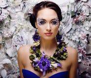 Art floral de visage avec l'anémone en bijoux, jeune femme sensuelle de brune Photographie stock libre de droits