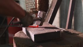 Blacksmith works hit hammer hot metal bar to bend it on anvil in forge workshop.