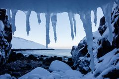 Art frame of white snow cold icicles on top foreground and stones beach of north arctic ocean with snowy cliff and mountain on the. Horizon with water royalty free stock images