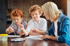 Concentrated brothers painting with granny at home Royalty Free Stock Images
