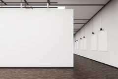 Art gallery with a blank wall and row of pictures. An art gallery interior. A large blank wall on the foreground. Row of pictures hanging on a wall. Concept of Royalty Free Stock Photography