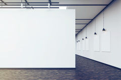 Art gallery with a blank wall and row of pictures, toned. An art gallery interior. A large blank wall on the foreground. Row of pictures hanging on a wall Stock Image