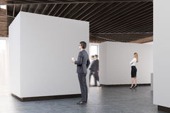 Art gallery concrete floor, side view, people. People are standing in an art gallery interior. White walls, concrete floor and wooden ceiling. Side view. Concept Stock Photo