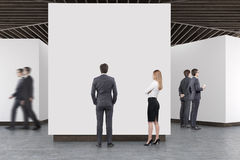 Art gallery concrete floor, wooden ceiling, people. People are standing in an art gallery interior. White walls, concrete floor and wooden ceiling. Concept of Stock Photos