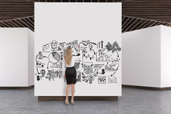 Art gallery concrete floor, wooden ceiling, plan. Rear view of a woman drawing a sketch in an art gallery interior. White walls, concrete floor and wooden royalty free stock photography