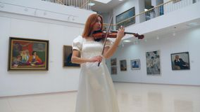 Art gallery with a female musician playing the violin. 4K stock footage
