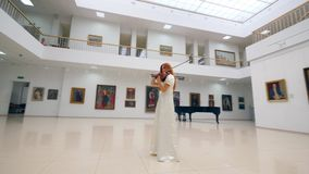 Art gallery with a lady playing the violin professionally stock video