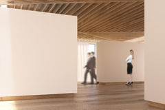 Art gallery wooden floor, ceiling, people walk. Men and a women are walking in an art gallery interior in chocolate tones. Beige walls, wooden floor and ceiling Royalty Free Stock Images