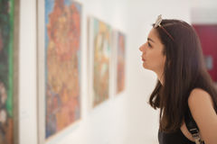 Art gallery. Young woman looking at modern painting in art gallery Royalty Free Stock Images