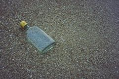 Art of glass bottle on sand beach. Glass bottle on the sand beach royalty free stock photography