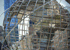 Art globe sculpture with a blue glass building in the background. Metallic silver public art globe sculpture with a blue glass building in the background Royalty Free Stock Image