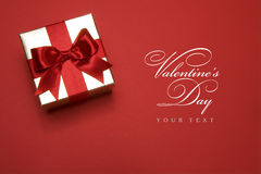 Art golden gift box. Golden gift box with a red bow on red background Stock Images