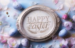 Happy Easter Background; Easter egg and spring flowers on blue t royalty free stock photos