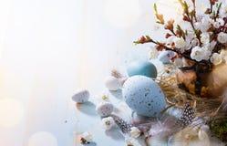 Art Happy Easter; Påskägg och kvistblommor på blå bakgrund arkivfoto
