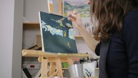 Art is her life. Creating artworks is her way of life. Woman painter working on landscape painting in oil stock footage