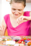 Art and hobby. A young woman working with her beads, making jewels Stock Photos