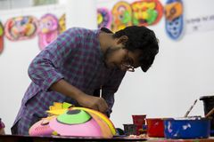 Art institute student painting a colorful lion face mask. Dhaka, Bangladesh. 12th Apr, 2016. Dhaka University Fine Arts FFA student paints a mural to celebrate stock photography