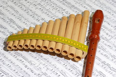 Art instruments. Panpipe with recorder on a note sheet royalty free stock photo