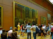 Art Interior Louvre Museum. Art patrons looks at painting hanging on the wall of the historic Louvre Museum royalty free stock photo