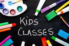 Art - Kids Classes. Handwritten on chalkboard surrounded by art equipment royalty free stock image