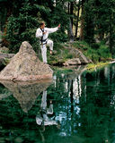 Art By The Lake. Man demonstrates Tae Kwon Do block while balanced on a rock. Image reflected in the lake Royalty Free Stock Photos