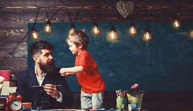 Art lesson concept. Child and teacher on busy face painting, drawing. Talented artist spend time with son. Teacher with. Beard, father teaches little son to royalty free stock images